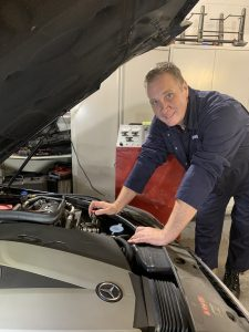Lea looking under bonnet and fixing car at Euromotors